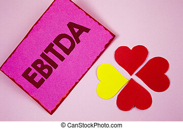 Word writing text Ebitda. Business concept for Earnings before tax is measured to evaluate company performance written on Sticky note paper on plain Pink background Paper Hearts next to it.