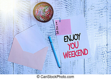 Word writing text Enjoy Your Weekend. Business concept for wishing someone that something nice will happen at holiday Envelope sheet paper sticky note ballpoint clips holder wooden background.