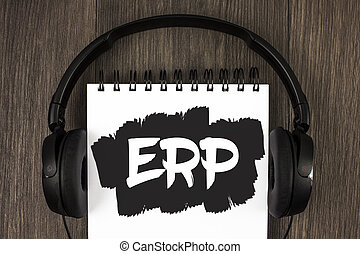 Word writing text Erp. Business concept for Enterprise resource planning with automate back office functions written on Notepad on the wooden background Headphone next to it.