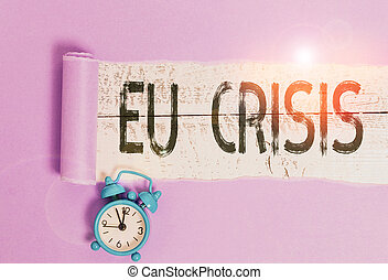 Word writing text Eu Crisis. Business concept for eurozone state unable to repay or refinance their government debt Alarm clock and torn cardboard placed above a wooden classic table backdrop.