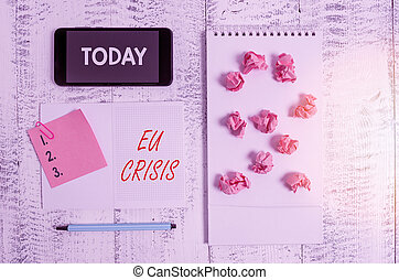Word writing text Eu Crisis. Business concept for eurozone state unable to repay or refinance their government debt Squared spiral notebook marker smartphone paper balls note clip wooden.