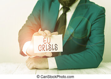 Word writing text Eu Crisis. Business concept for eurozone state unable to repay or refinance their government debt Man holds empty paper with copy space in front of him Space.
