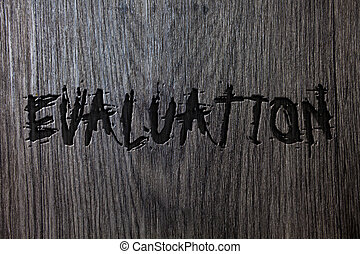 Word writing text Evaluation. Business concept for Judgment Feedback Evaluate the quality performance of something Wooden wood background black engraved letters words ideas messages concepts.
