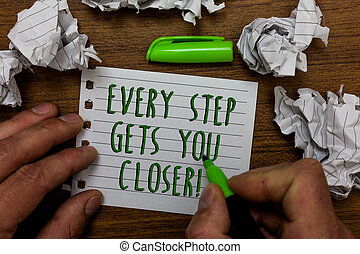 Word writing text Every Step Gets You Closer. Business concept for Keep moving to reach your goals objectives Hand hold green pen and words on white page paper lobs around on wooden desk.