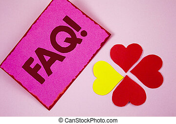 Word writing text Faq Motivational Call. Business concept for Frequently asked question for clearing up confusions written on Sticky note paper on plain Pink background Paper Hearts next to it.