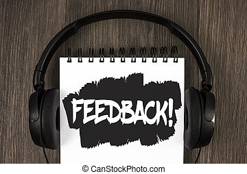 Word writing text Feedback Motivational Call. Business concept for Rating an economical local grocery store written on Notepad on the wooden background Headphone next to it.
