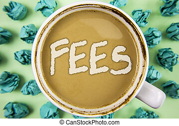 Word writing text Fees. Business concept for Online creative agency charges product components hourly costs written on Tea in White Cup within Crumpled Paper Balls on plain background.
