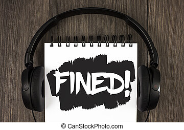 Word writing text Fined Motivational Call. Business concept for No penalty charge for late credit card bill payment written on Notepad on the wooden background Headphone next to it.