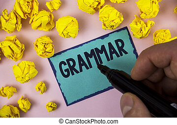 Word writing text Grammar. Business concept for System and Structure of a Language Correct Proper Writing Rules written by Man on Sticky note paper holding Marker plain background Paper Balls.