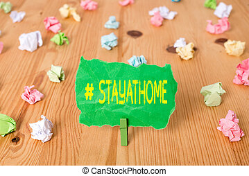 Word writing text Hashtag Stay at home. Business concept for a trending label in social media related to the coronvirus outbreak Colored crumpled papers empty reminder wooden floor background clothespin.