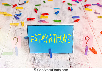 Word writing text Hashtag Stay at home. Business concept for a trending label in social media related to the coronvirus outbreak Scribbled and crumbling sheet with paper clips placed on the wooden table.