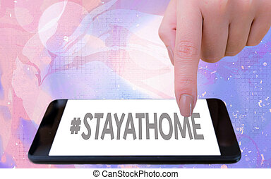 Word writing text Hashtag Stay at home. Business concept for a trending label in social media related to the coronvirus outbreak Modern gadgets with white display screen under colorful bokeh background.