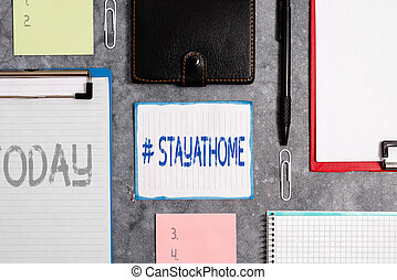 Word writing text Hashtag Stay at home. Business concept for a trending label in social media related to the coronvirus outbreak Paper accesories with digital smartphone arranged on different background.