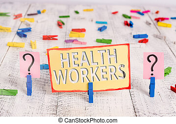 Word writing text Health Workers. Business concept for showing whose job to protect the health of their communities Scribbled and crumbling sheet with paper clips placed on the wooden table.