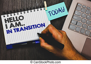 Word writing text Hello I Am.. In Transition. Business concept for Changing process Progressing planning new things Paperclip grip sticky note with text hand hold pen computer on wooden desk.