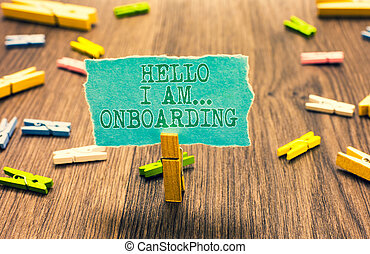 Word writing text Hello I Am... Onboarding. Business concept for telling person that you are on ship or plane Clothespin holding turquoise paper note several clothespins wooden floor.