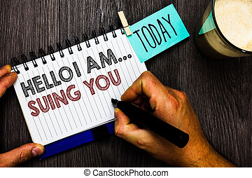 Word writing text Hello I Am... Suing You. Business concept for create a case to accuse someone from his actions Man holding marker notebook clothespin hold reminder coffee cup wood table.