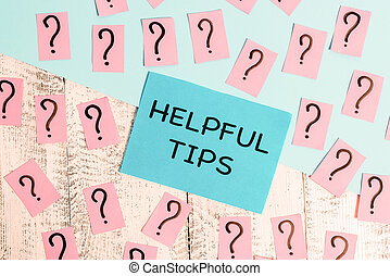 Word writing text Helpful Tips. Business concept for advices given to be helpful knowledge in life Scribbled and crumbling papers with thick cardboard above wooden table.
