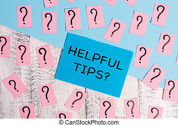 Word writing text Helpful Tips Question. Business concept for secret information or advice given to be helpful knowledge Scribbled and crumbling papers with thick cardboard above wooden table.