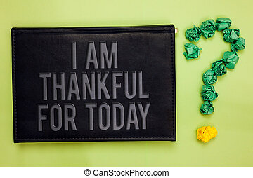 Word writing text I Am Thankful For Today. Business concept for Grateful about living one more day Philosophy Green back black plank with text green paper lob form question mark.