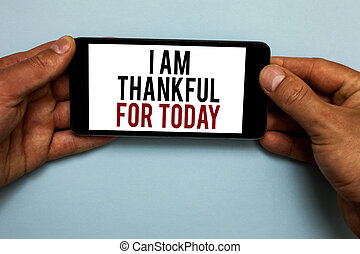 Word writing text I Am Thankful For Today. Business concept for Grateful about living one more day Philosophy Human hand hold smartphone with red and black letters on shadow blue floor.