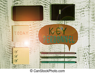 Word writing text Key Personnel. Business photo showcasing Program Directors Principal Investigator Project Executives Smartphone pens blank speech bubble sticky notes wallet wooden background