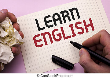 Word writing text Learn English. Business concept for Study another Language Learn Something Foreign Communication written by Man on Notebook Paper Holding Marker on the plain background.