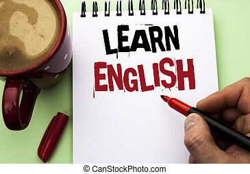 Word writing text Learn English. Business concept for Study another Language Learn Something Foreign Communication written by Man on Notebook Book Holding Marker on the plain background Coffee Cup