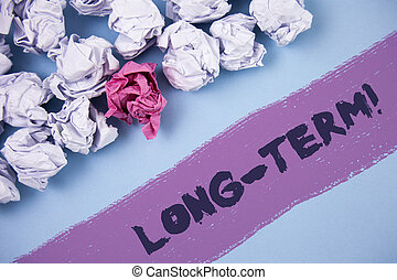 Word writing text Long-Term Motivational Call. Business concept for Occurring over large period of time Future plans written on Painted background Crumpled Paper Balls next to it.