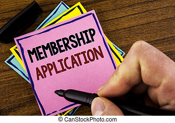 Word writing text Membership Application. Business concept for Registration to Join a team group or organization written by Man on Pink sticky note paper holding marker on wooden background