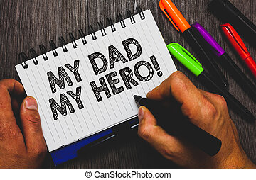 Word writing text My Dad My Hero. Business concept for Admiration for your father love feelings emotions compliment Hand holding pen and paper sketch words near lie some pen on woody desk.