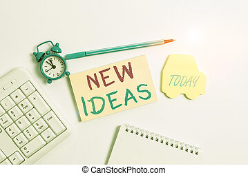Word writing text New Ideas. Business concept for something original or fresh and more effective innovation Copy space on empty note paper with clock and pencil on the table.