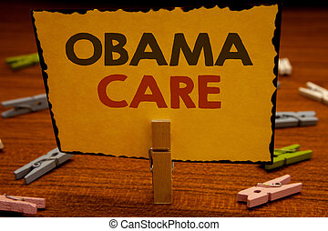 Word writing text Obama Care. Business concept for Government Program of Insurance System Patient ProtectionClothespin hold holding Yellow paper ideas clothespins wooden background.