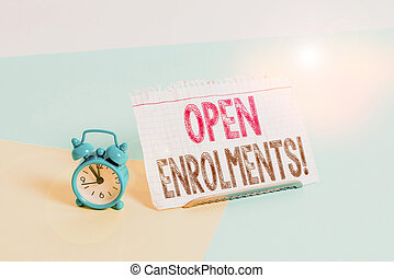 Word writing text Open Enrolments. Business concept for when employees may make changes to elected fringe benefit Mini size alarm clock beside a Paper sheet placed tilted on pastel backdrop.