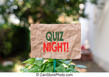 Word writing text Quiz Night. Business concept for evening test knowledge competition between individuals Plain empty paper attached to a stick and placed in the green leafy plants.