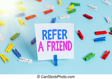 Word writing text Refer A Friend. Business concept for direct someone to another or send him something like a gift Colored clothespin papers empty reminder blue floor background office pin.