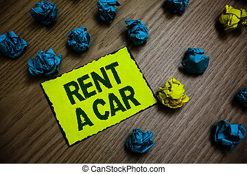 Word writing text Rent A Car. Business concept for paying for temporary vehicle usage from one day to months Yellow piece paper reminder lots crumpled papers several tries wooden floor.