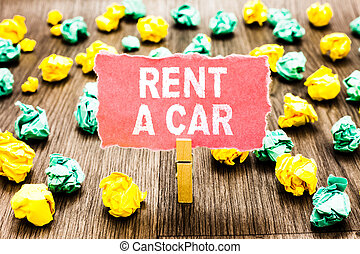 Word writing text Rent A Car. Business concept for paying for temporary vehicle usage from one day to months Clothespin holding pink note paper crumpled papers several tries mistakes.