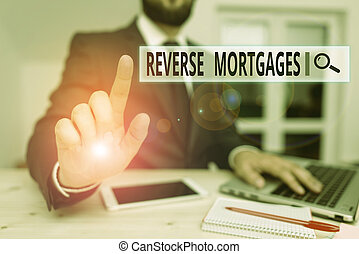 Word writing text Reverse Mortgages. Business photo showcasing borrower to access the unencumbered value of the property Male human wear formal clothes present presentation use hi tech smartphone