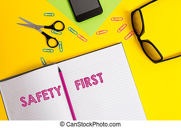 Word writing text Safety First. Business concept for used to say that the most important thing is to be safe Sheet pencil clips smartphone scissors eyeglasses notepad color background.