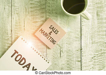 Word writing text Sales And Marketing. Business concept for Promotion Selling Distribution of Goods or Services Stationary placed next to a cup of black coffee above the wooden table.