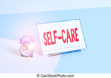 Word writing text Self Care. Business concept for practice of taking action to preserve or improve ones own health Mini size alarm clock beside a Paper sheet placed tilted on pastel backdrop.