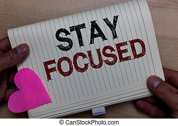 Word writing text Stay Focused. Business concept for Be attentive Concentrate Prioritize the task Avoid distractions Man holding notebook paper heart Romantic ideas messages Wooden background.
