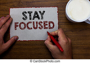 Word writing text Stay Focused. Business concept for Be attentive Concentrate Prioritize the task Avoid distractions Man holding marker communicating ideas piece paper wooden table cup coffee.