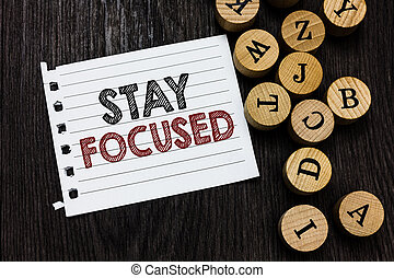 Word writing text Stay Focused. Business concept for Be attentive Concentrate Prioritize the task Avoid distractions Piece notebook paper circle letters ideas inspiration wooden background.