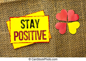 Word writing text Stay Positive. Business concept for Be Optimistic Motivated Good Attitude Inspired Hopeful written on Sticky Note Paper on the jute background Love Hearts next to it.
