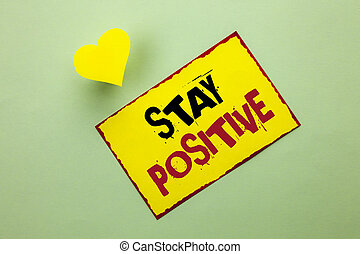 Word writing text Stay Positive. Business concept for Be Optimistic Motivated Good Attitude Inspired Hopeful written on Yellow Sticky Note Paper on the Plain background Heart next to it.