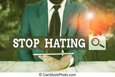 Word writing text Stop Hating. Business concept for to drop all standards and wholeheartedly agree without question Businessman with mobile phone in his hand.