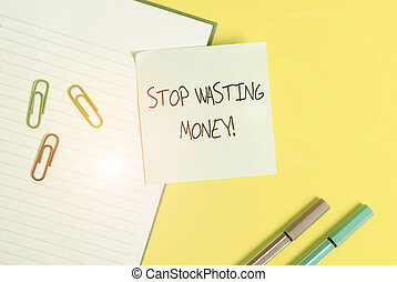 Word writing text Stop Wasting Money. Business concept for advicing demonstrating or group to start saving and use it wisely Empty blue paper with copy space paper clips and pencils on the yellow table.