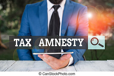 Word writing text Tax Amnesty. Business concept for limitedtime opportunity for specified group of taxpayers to pay Businessman with mobile phone in his hand.